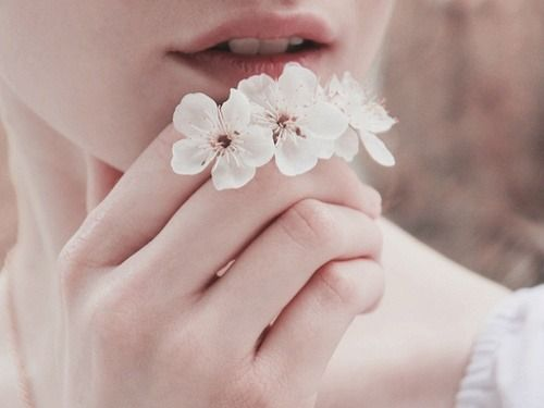 女性の口元に花