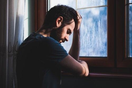 窓辺で悩む男性