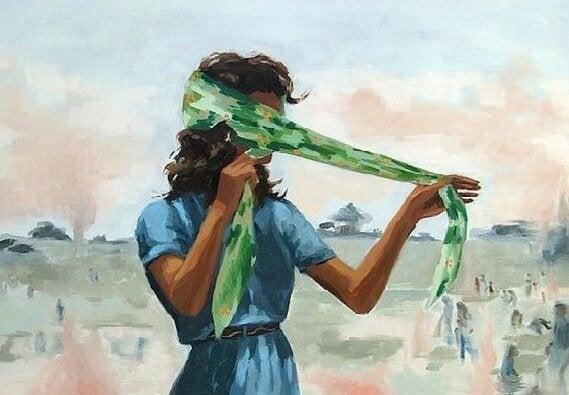 緑の布で目隠しをする女性