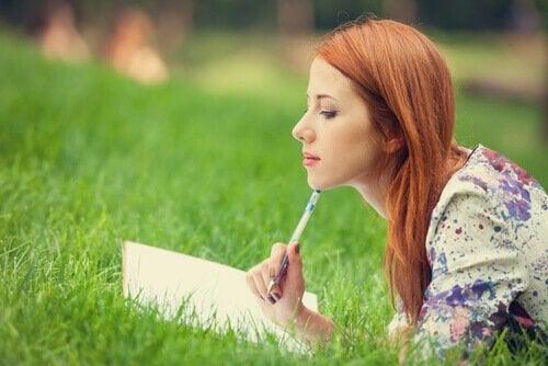 芝生で日記をつける女性
