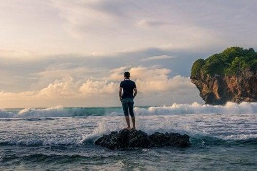 海辺の岩の上に立つ男