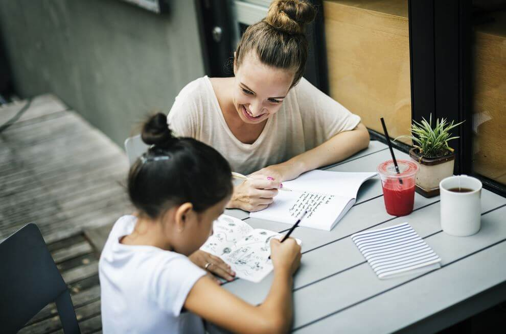 母親と娘が一緒に宿題をしている