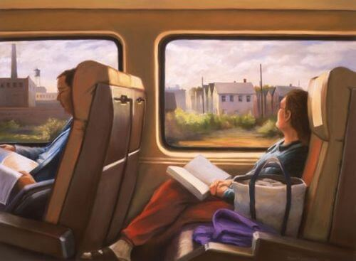 本を手に車窓を眺める女性