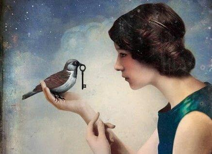 鍵をくわえた鳥が女性の手に乗っている