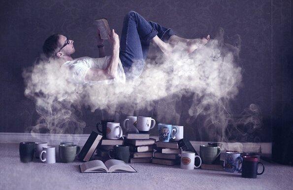 コーヒーの湯気の上で本を読む男性