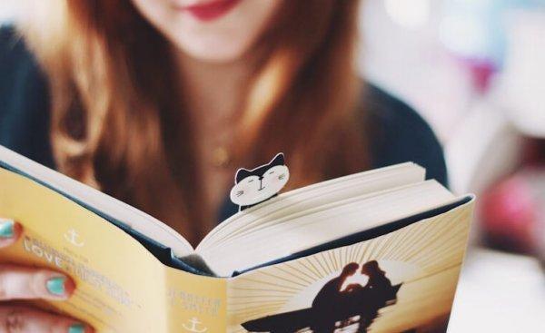 猫のしおりを挟んだ本を読む女性