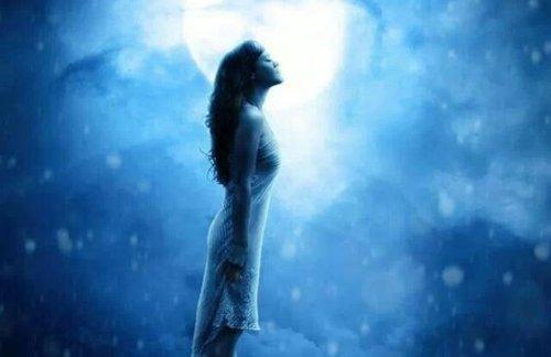 月の前に立つ女性