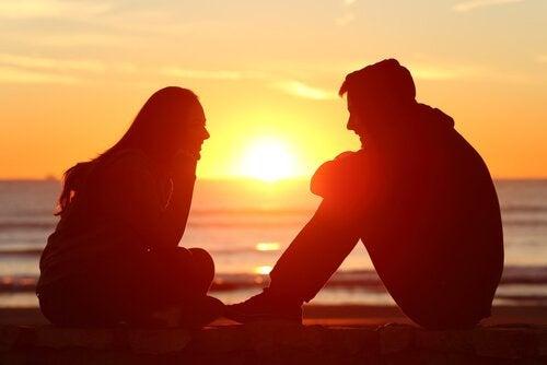 夕日をバックにカップルが話している