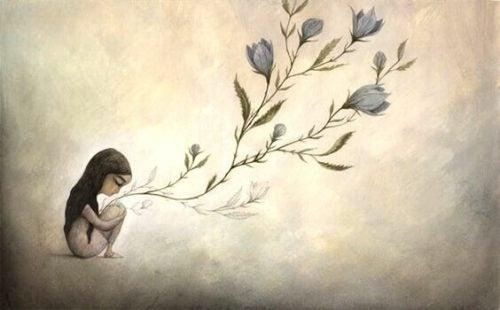 座り込む女の子から花が咲く