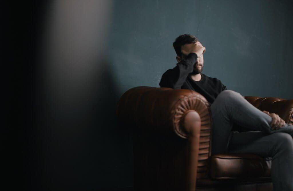 椅子に座り悩む男性