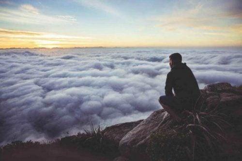 山頂で雲を見つめる男性