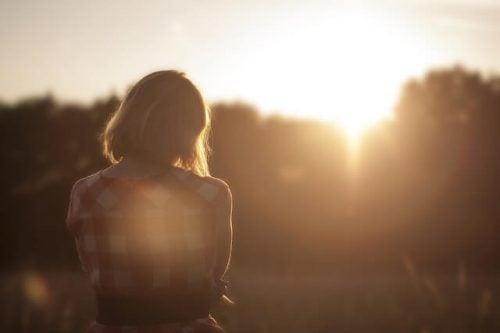 夕陽を見つめる悲しい女性