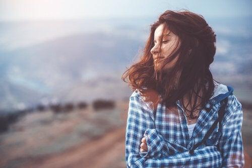 山で目を閉じる女性