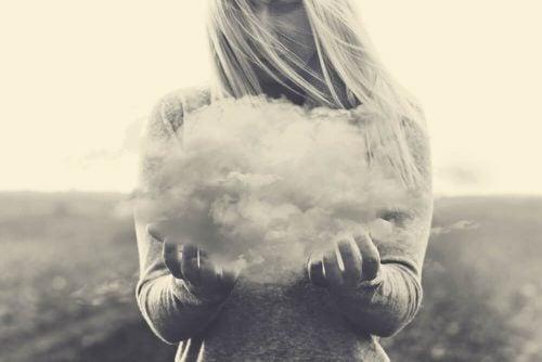 否定的な考えを表す雲を持つ女性
