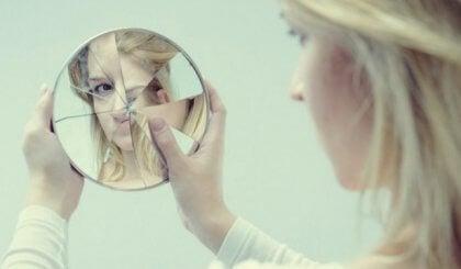 割れた鏡を見る女性