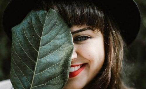 葉で顔を隠す女性