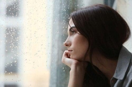 窓の外の雨を見つめる女性