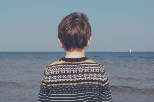 海を見つめる子供の後ろ姿